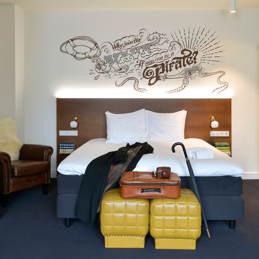 Heerlijk bed en funky muurtekening in de Large Deluxe hotelkamer